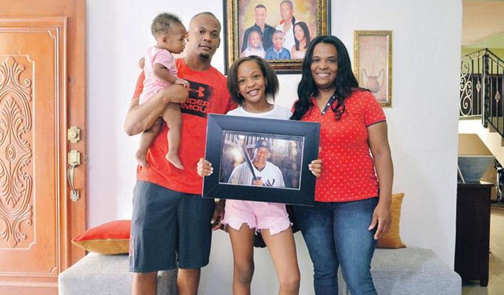 Hoany Lisandra Ruiz, junto a sus hijos Joan y Angélica muestran una foto de Andújar en su hogar en esta comunidad.