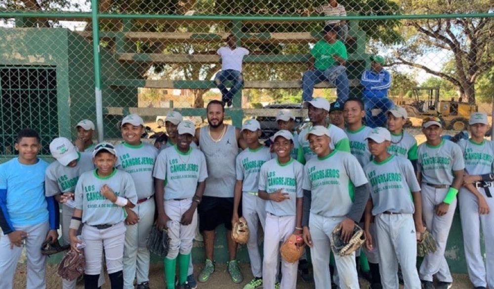 Jordany Valdespín junto a los niños de la Escuela de Beisbol Cangrejeros de la comunidad de Las Caobas