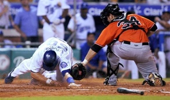 Jake Fox, del Licey, es puesto out en la goma por el receptor Dustin Brown, de los Toros en el segundo inning.