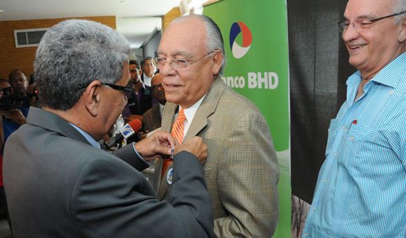 Luis Catano, ejecutivo de los Toros del Este, impone la medalla a Frank Micheli